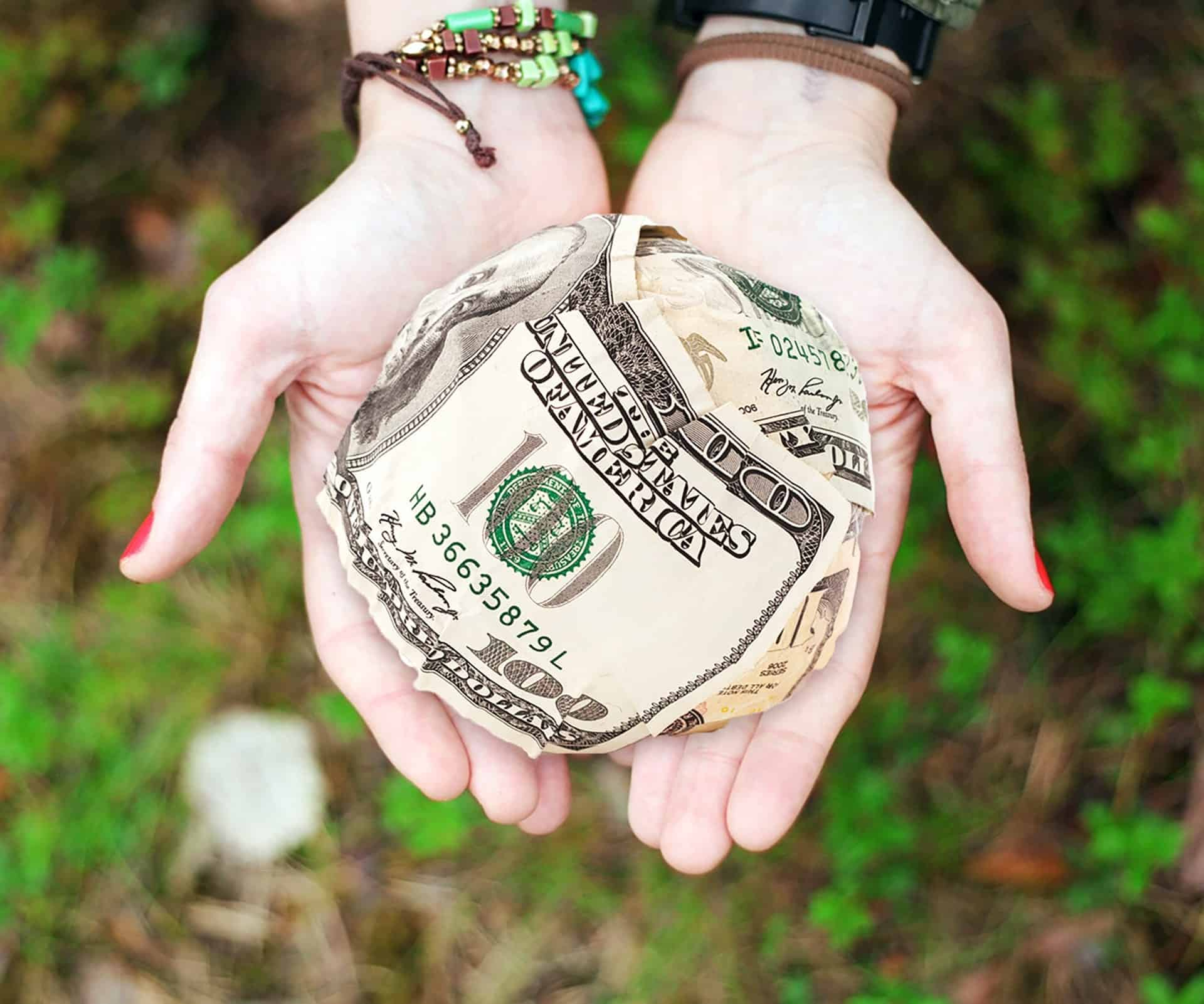 woman holding a ball made out of money
